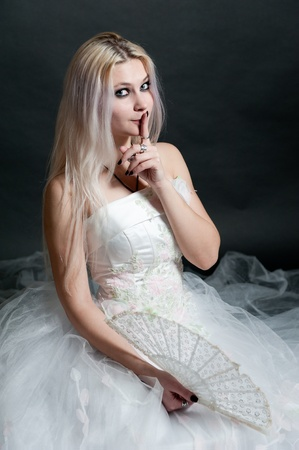 Beautiful girl in white dress with fan on black background Stock Photo