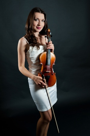 solo violinist: Girl violinist in white dress on black background
