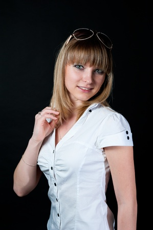 medium length: Blond girl in shirt and jeans on black background Stock Photo