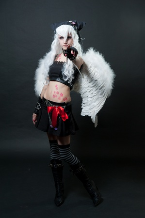 Girl in cosplay suit on black background photo