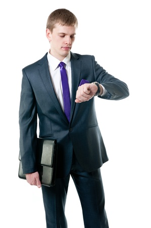 The young businessman in a suit looking at the watch isolated on white background Stock Photo