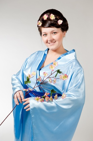 woman in blue kimono with a branch of cherry blossoms . photo