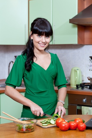 beautiful woman cooking healthy food in the kitchen - indoors photo