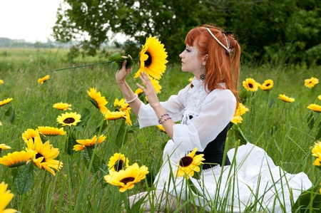 red-haired nymph in a white dress on a fairy glade photo