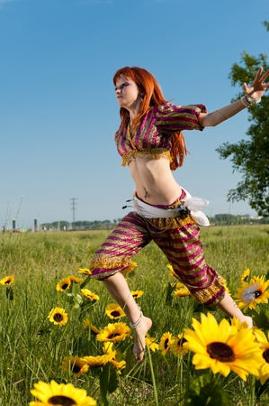 eastern red-haired fairy in the magical meadow with sunflowers photo