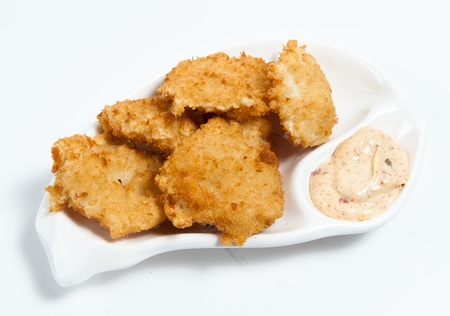 nuggets: chicken nuggets with sauce on the plate isolated on white