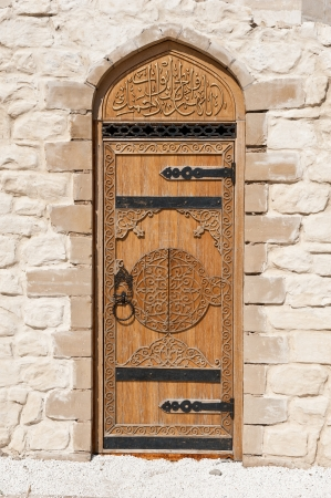 door leaf: door with Arabic script in the stone wall