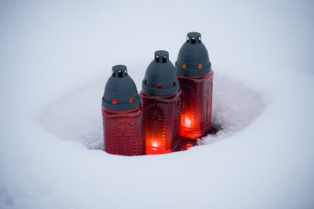 The candles covered by the snow on the cementery photo