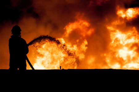 fire damage: Fireman working in the night at the explosion Stock Photo