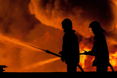 bombero de rojo: Bombero trabajando en la noche en la explosi�n