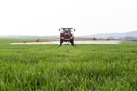 cultivator: Spraying the herbicides on the green field Stock Photo