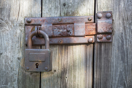 Old metal padlock on the wooden door photo