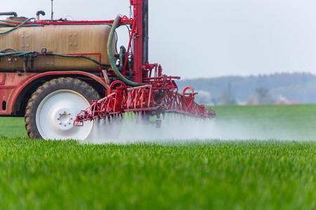 farm worker: Spraying machine working on the green field