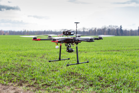 drones: The small dron hexcopter flying over the field