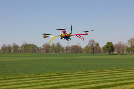 heli: The quadrocopter flying over the green field Stock Photo