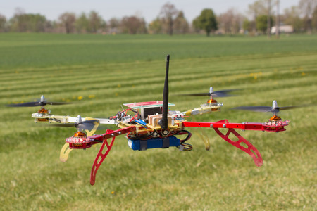 El quadrocopter volando sobre el campo verde Foto de archivo - 34714056