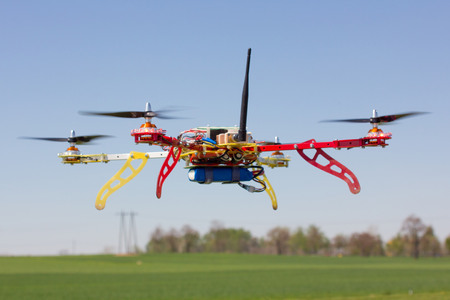 drones: The quadrocopter flying over the green field Stock Photo