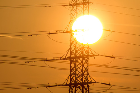electricity providers: The sunset over the field and the powerlines Stock Photo