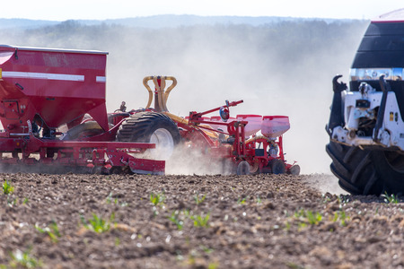 harrowing: The tractor harrowing the large brown field in spring season Stock Photo