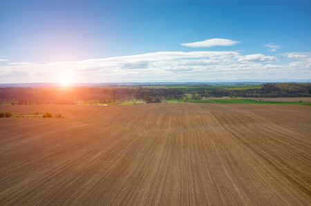 harrowing: Aerial view of the sunset above the tractor harrowing the large brown field in spring season