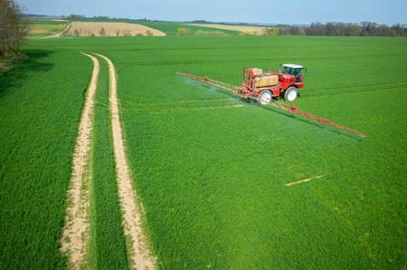 大規模なグリーン フィールド上の化学物質の散布トラクターの航空写真