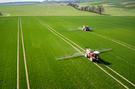 Luchtfoto van de trekker sproeien van de chemicaliën op het grote groene veld