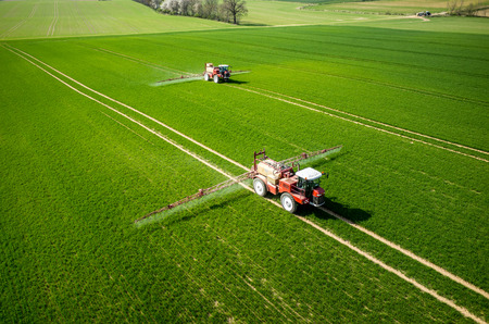 chemical plant: Aerial view of the tractor spraying the chemicals on the large green field