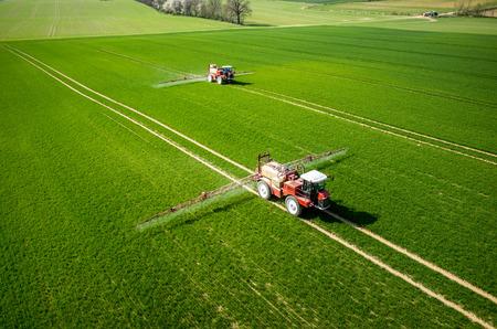 cenital: Vista aérea del tractor de fumigación de los productos químicos en el gran campo verde