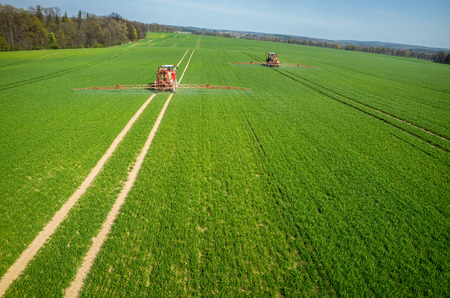 crop sprayer: Aerial view of the tractor spraying the chemicals on the large green field