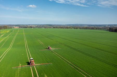 Luchtfoto van de trekker die de chemicaliën op het grote groene veld bespuit