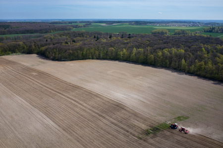 harrowing: Aerial view of the the tractor harrowing the large brown field in spring season Stock Photo