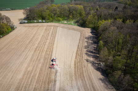 harrowing: Aerial view of the the tractor harrowing the large brown field in spring season Foto de archivo