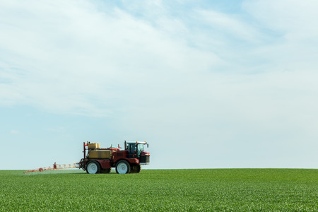 agricultural implements: Spraying the herbicides on the green field Stock Photo