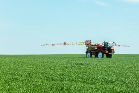 Rociar los herbicidas en el campo verde