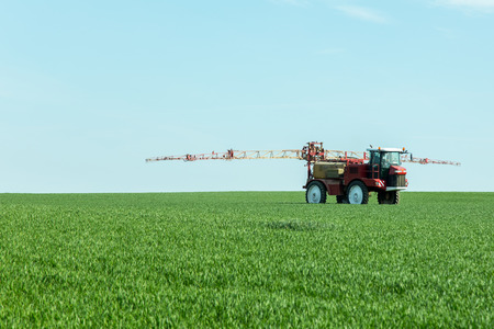 agriculture machinery: Spraying the herbicides on the green field Stock Photo