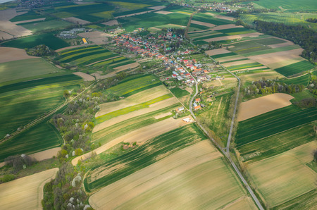 Luchtfoto van een klein dorp, omringd door groene velden