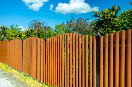 Long brown wooden fence protecting private property Standard-Bild