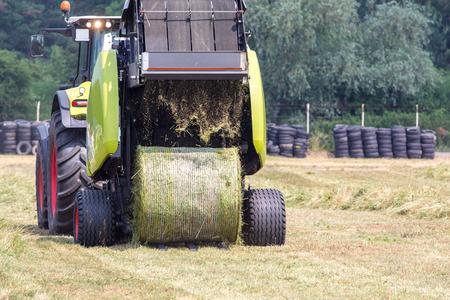 baler: Round baler working on the green field