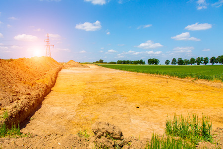 agriculture machinery: Beautiful sunset above the road under construction Stock Photo