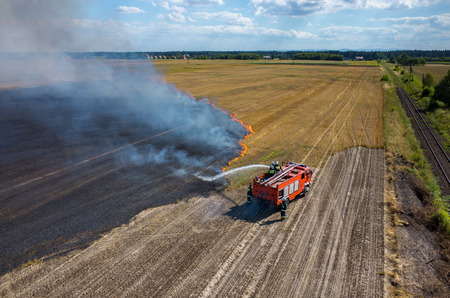 fire smoke: Aerial view on the fireman truck working on the field on fire