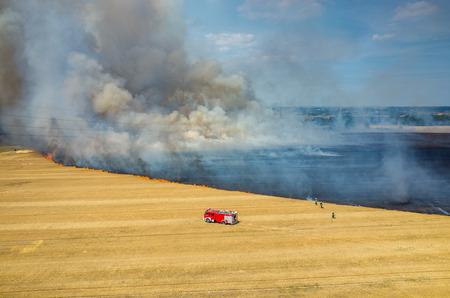 camion de bomberos: Vista aérea en el camión bombero que trabaja en el campo en llamas Foto de archivo