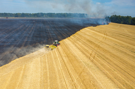 harrowing: The tractor harrowing the large field to stop the fire Stock Photo