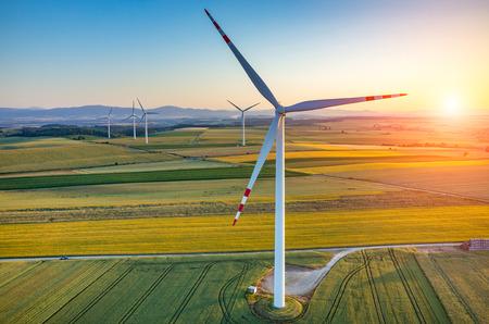 turbina: Hermosa puesta de sol sobre los molinos de viento en el campo