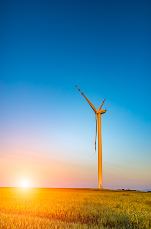 フィールド上の風車の上の美しい日没 写真素材