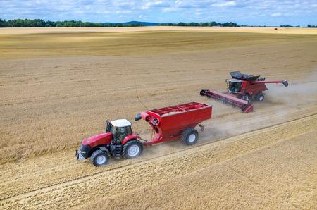 Luchtfoto van de combines en tractoren te werken op het grote tarweveld