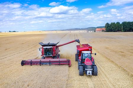 cosechadora: Vista aérea de las cosechadoras y tractores que trabajan en el campo de trigo grande Foto de archivo