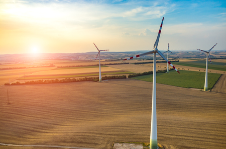 power nature: Beautiful sunset above the windmills on the field