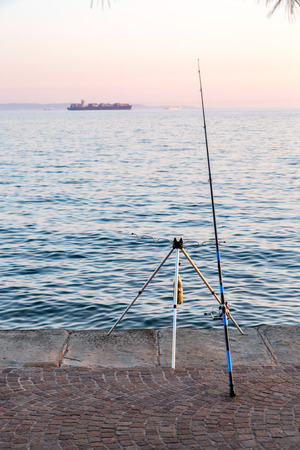 rhodium: Large view on the fishing rod at the oceans shore