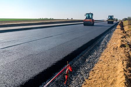 Apisonadoras construcción de la nueva carretera de asfalto Foto de archivo - 47937553