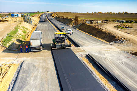 Aerial view on the road rollers building the new asphalt road